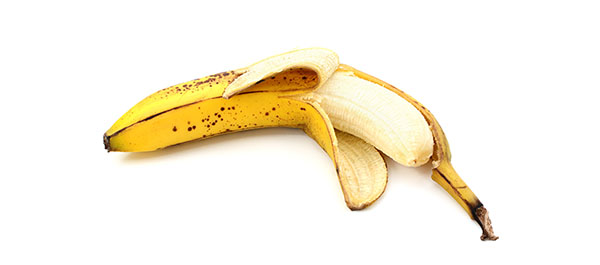 Half-peeled overripe, spotty banana, isolated on a white background