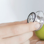 close up of male doctor with green apple and stethoscope